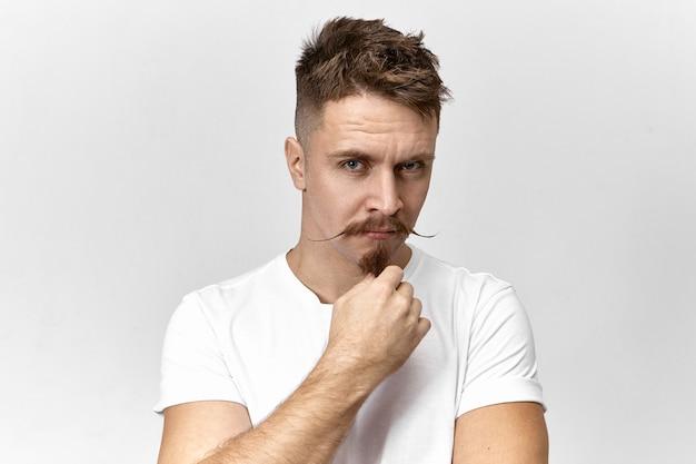 彼のひげに手をつないで、疑いと不信感を持ってカメラを見つめている白いtシャツを着た疑わしい深刻な若いヨーロッパ人の肖像画。屋内でポーズをとるスタイリッシュな口ひげを持つ物思いにふけるひげを生やした男