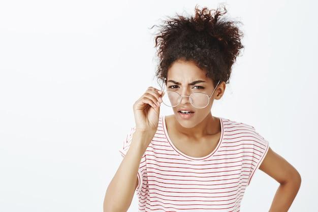 スタジオでポーズをとってアフロの髪型を持つ不審な女性の肖像画