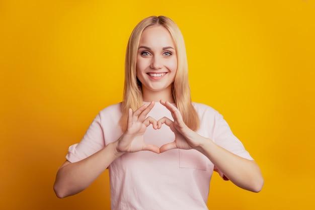 달콤한 사랑스러운 귀여운 소녀의 초상화는 노란색 배경에 심장 기호 이빨 미소를 보여줍니다