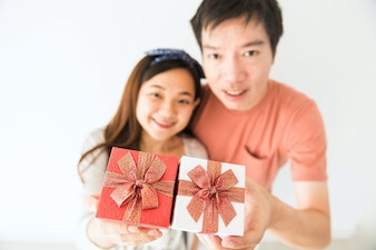 Portrait of sweet Asian couple holding surprise gift box