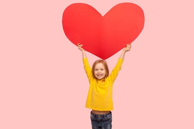 머리 위로 큰 붉은 심장 기호를 들고 카메라에 미소 짓고, 어머니의 날에 축하하며 사랑한다고 말하는 귀엽고 쾌활한 어린 소녀의 초상화. 분홍색 배경에 고립 된 실내 스튜디오 촬영