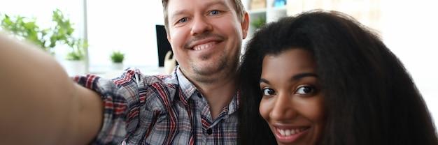 スマートフォンでselfieを作る甘いカップルの肖像画。笑みを浮かべて男とアフリカ系アメリカ人の女性。機嫌の良い配偶者。関係とレジャーの楽しい時間一緒にコンセプト