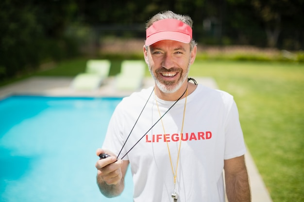 プールサイドの近くにストップウォッチを保持している水泳コーチの肖像画