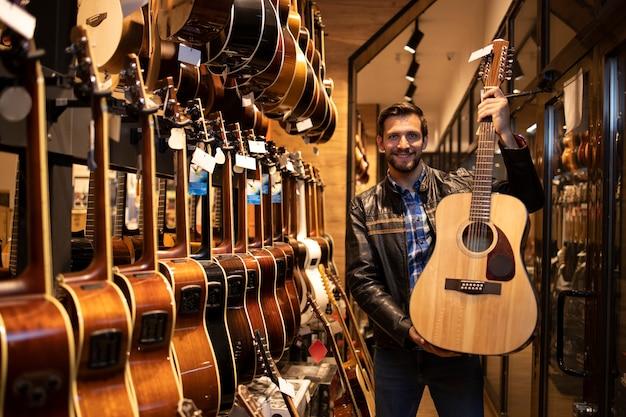 Портрет талантливого кавказского музыканта в кожаной куртке, стоящего в музыкальном магазине и держащего классическую акустическую гитару для продажи.
