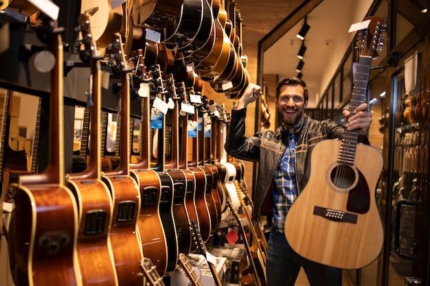 Портрет талантливого кавказского музыканта в кожаной куртке, который только что купил в музыкальном магазине классическую акустическую гитару.
