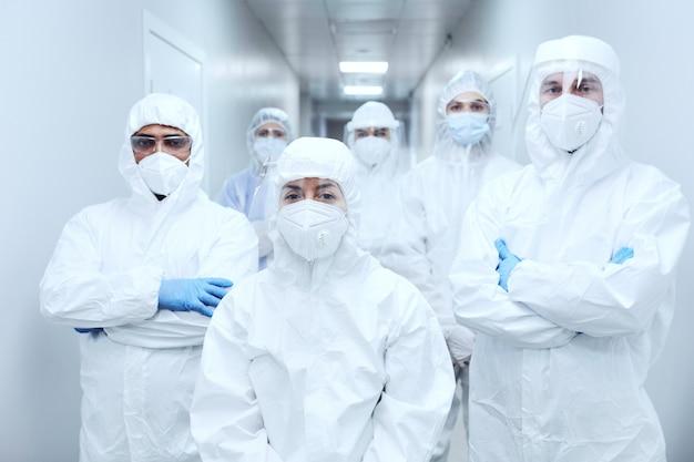 코로나바이러스 전염병 동안 일하는 동안 카메라를 바라보는 보호복과 마스크를 쓴 의사 팀의 초상화