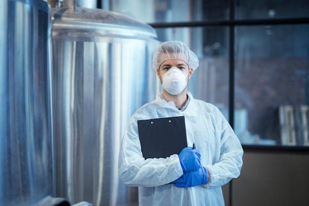 Портрет технолога в белой форме с сеткой для волос, защитной маской и перчатками, стоящего на фармацевтическом или пищевом заводе со скрещенными руками