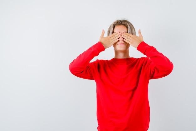 赤いセーターの手で目を覆い、スリル満点の正面図を見て十代の少年の肖像画