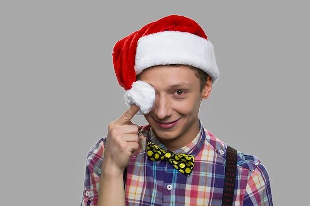 재미 산타 모자에 십 대 소년의 초상화. 미소로 카메라를보고 산타 모자에 크리스마스 소년.