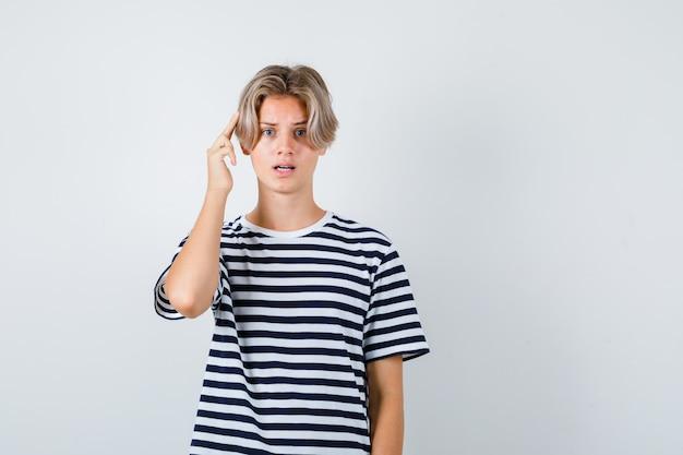 티셔츠에 머리에 손가락을 대고 어리둥절한 앞모습을 보고 있는 십대 소년의 초상화
