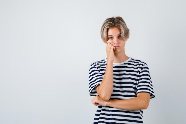 Tシャツで頬に手を保ち、思慮深い正面図を探している10代の少年の肖像画