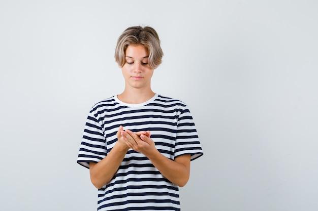 티셔츠를 입은 손바닥을 보고 조심스럽게 정면을 바라보는 십대 소년의 초상화