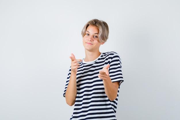 Портрет мальчика подростка, указывая вперед в футболке и глядя веселый вид спереди