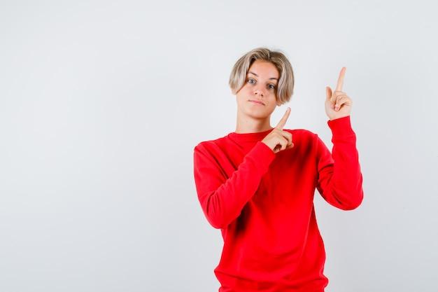赤いセーターで上向きで自信を持って正面を見て10代の少年の肖像画