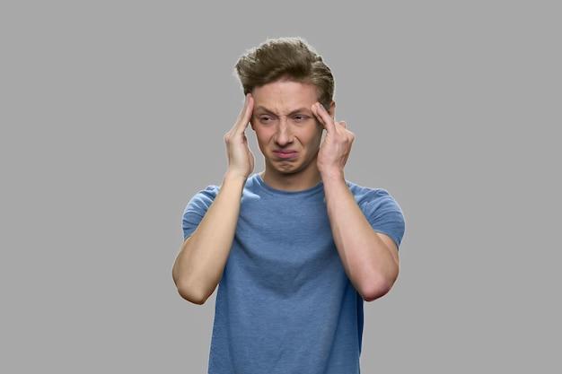 십 대 소년의 초상화는 두통을 앓고 있습니다. 회색 배경에 편두통 통증 데 십 대 소년. 스트레스 개념.