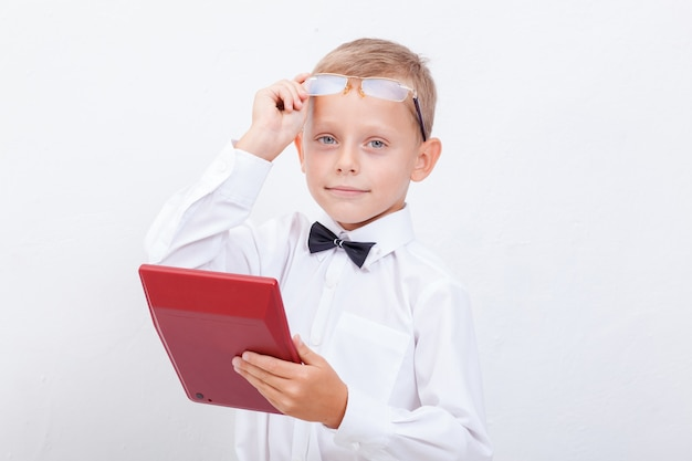 白い背景の上の電卓を持つ10代の少年のポートレート