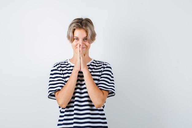 Tシャツでジェスチャーを祈り、感謝の気持ちを込めて正面から見ている手で十代の少年の肖像画