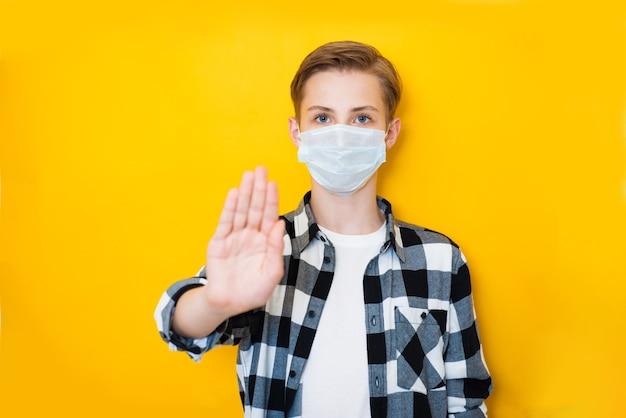 Портрет мальчика подростка с хирургической медицинской маской, стоящей с рукой стопа и смотрящей в камеру.