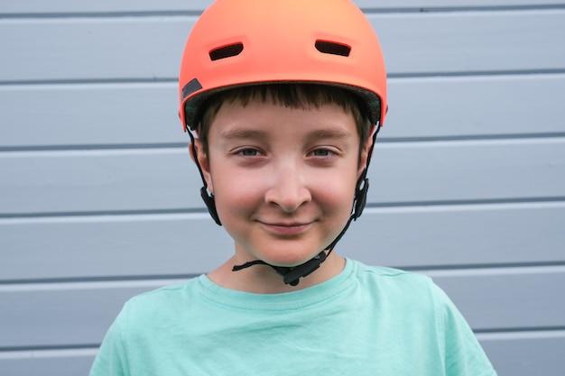 オレンジ色のスポーツクラッシュヘルメットを身に着けている10代の白人少年の肖像画、夏に自転車やスケートボードに乗ることを学び、屋外の子供たちの活動中に安全と保護。