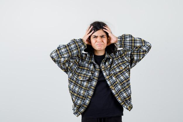カジュアルなシャツの手で頭を握りしめ、失望した正面図を探している十代の少女の肖像画