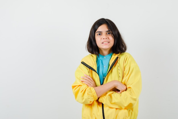 黄色のジャケットで腕を組んで、忘れられた正面図を探している十代の少女の肖像画