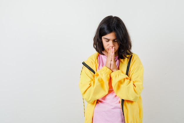 Tシャツ、黄色のジャケットで祈りのジェスチャーで手をつないで、焦点を絞った正面図を探している10代の少女の肖像画