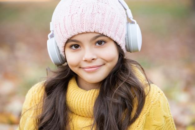 帽子をかぶった十代の少女の肖像画。陽気な子供は屋外のヘッドフォンで音楽を聴きます。秋の自然。 9月。学校に戻る。自然の美。秋のファッション。