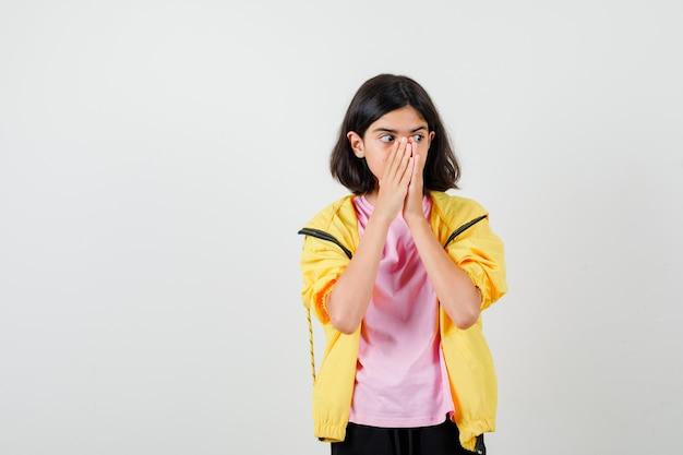 Портрет девушки-подростка, держащей руки на лице в футболке, куртке и испуганной вид спереди