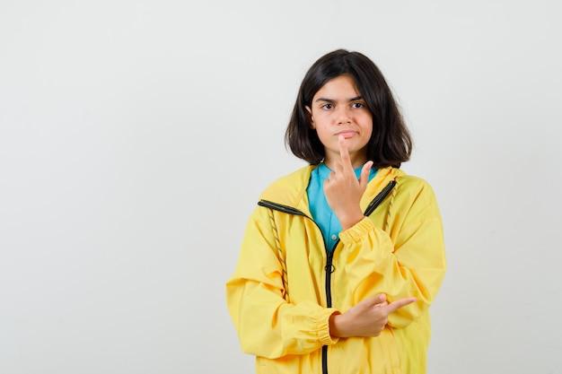 シャツ、黄色のジャケットを右に向け、躊躇している正面図を見ながら銃のジェスチャーを示す十代の少女の肖像画