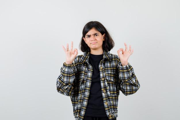 캐주얼 셔츠에 확인 제스처를 보이고 주저하는 전면 보기를 보여주는 10대 소녀의 초상화