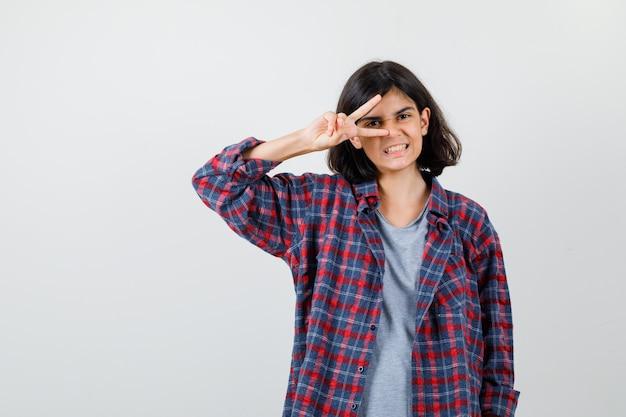 カジュアルな服装で目にvサインを示し、陽気な正面図を探している10代の少女の肖像画