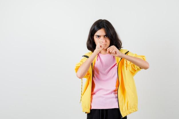 Портрет девушки-подростка, стоящей в боевой позе в футболке, куртке и смотрящей сфокусированным видом спереди