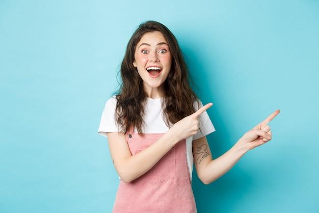 곱슬머리와 매력적인 10대 행복한 여성의 초상화는 로고 배너를 손가락으로 가리키고, 발표하고, 광고를 보여주고, 파란색 배경을 보여줍니다.