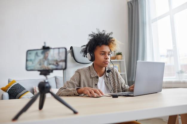 自宅でビデオゲームをストリーミングしながらヘッドセットを着用し、ラップトップを使用している10代のアフリカ系アメリカ人の少年の肖像画、若いゲーマーまたはブロガーのコンセプト、コピースペース