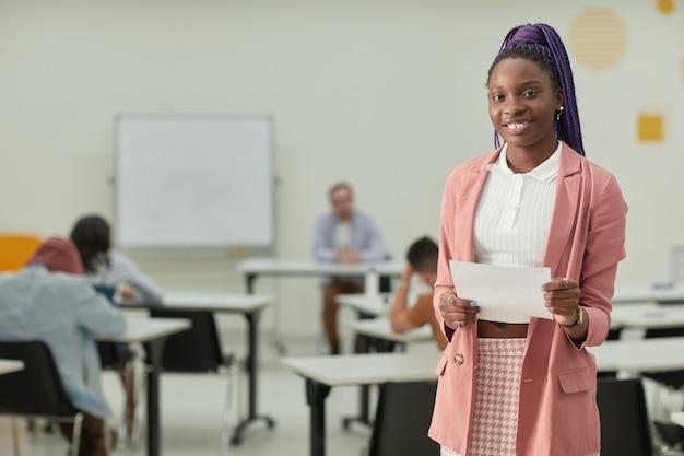 Портрет афро-американской девочки-подростка в школьном классе, счастливо улыбающейся в камеру и держащей тестовый сертификат, копией пространства
