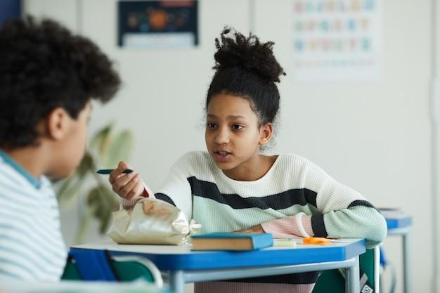学校の教室、コピースペースで友人と話している10代のアフリカ系アメリカ人の女の子の肖像画