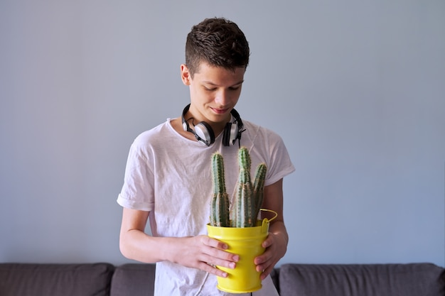彼の手でサボテンの鍋、灰色の背景を保持しているヘッドフォンで16歳の10代の少年の肖像画