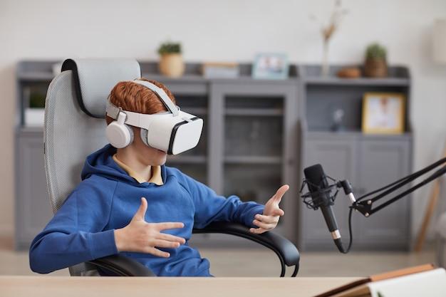 Портрет мальчика-подростка в гарнитуре vr и говорящего в микрофон, играя в иммерсивные видеоигры во время потоковой передачи онлайн, скопируйте пространство