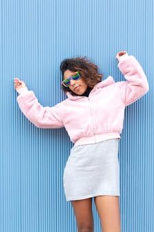 Портрет подростковой девушки брюнет представляя на синем фоне. она носит неформальную одежду и солнцезащитные очки с цветами флага лгбт. место для текста.