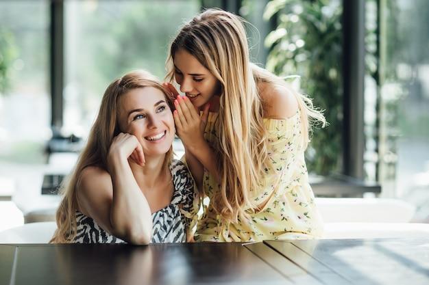 ストリートカフェで一緒に昼食をとっている10代の娘と彼女の母親の肖像画
