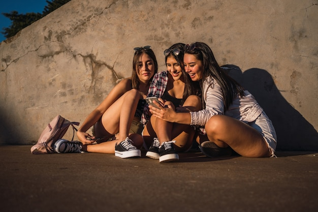 도시 공원에서 smarthphone보고 앉아 십 대 친구의 초상화
