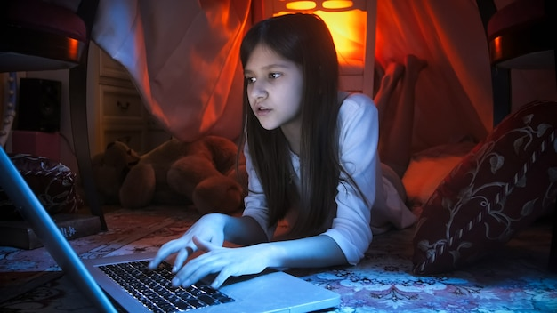 침실에서 카펫에 누워 하 고 밤에 노트북을 사용하는 십 대 소녀의 초상화.