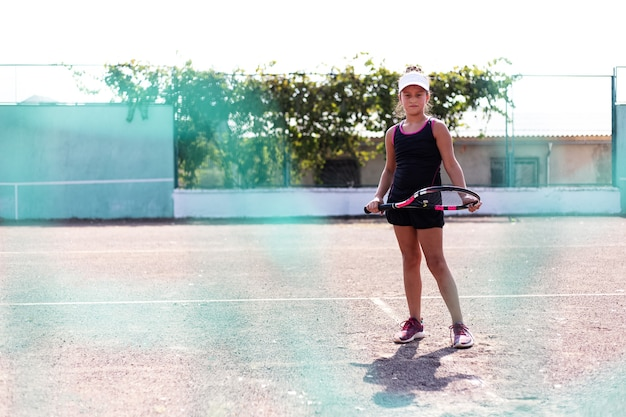 スポーツコートでテニスをしている10代の少女の肖像画