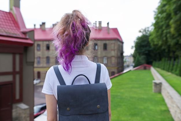 학교 건물을 바라보며 서 있는 배낭을 메고 있는 10대 소녀의 초상화. 다시 학교로, 다시 대학으로, 교육, 학습, 어린이, 십대 개념