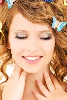 Портрет девочки-подростка с бабочками над белой стеной