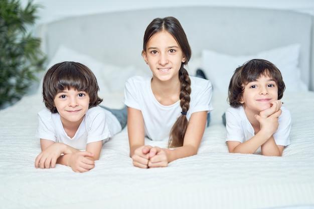 10대 라틴 소녀와 카메라를 보며 웃고 있는 두 소년의 초상화. 자매는 집에서 침대에 누워 귀여운 형제들과 시간을 보내고 있습니다. 행복한 아이들 개념