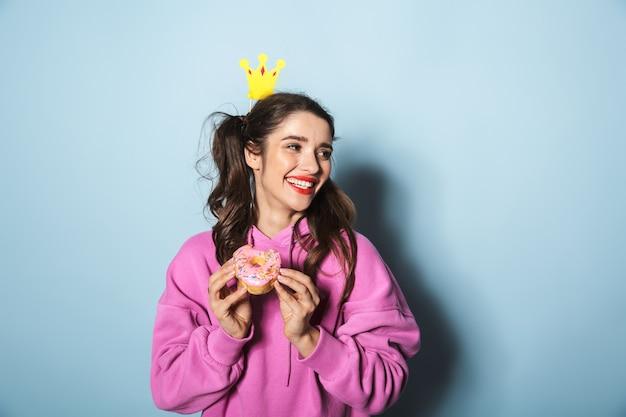 Портрет девочки-подростка с двумя хвостиками, держащей сладкий пончик и коронную палочку над синим в студии