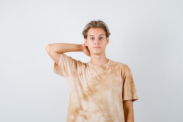 Портрет мальчика-подростка, держащего руку за шею в футболке и выглядящего умным спереди