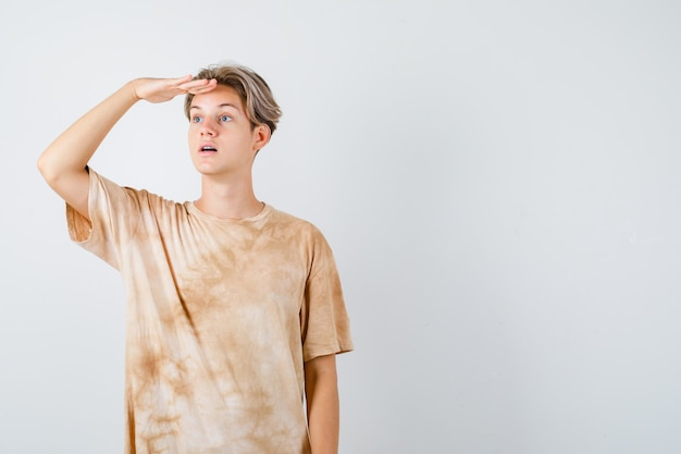 Портрет мальчика-подростка, смотрящего вдаль, положив руку на голову в футболке и смотрящего с удивлением на вид спереди