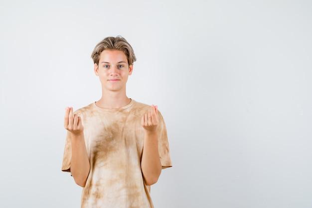 Портрет мальчика-подростка, делающего денежный жест в футболке и веселого вида спереди